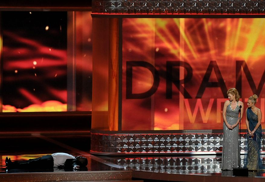 Tracy Morgan (left) lies on the floor as Connie Britton (center) and Hayden Panettiere present an award onstage at the 64th Primetime Emmy Awards at the Nokia Theatre on Sunday, Sept. 23, 2012, in Los Angeles. (John Shearer/Invision/AP)
