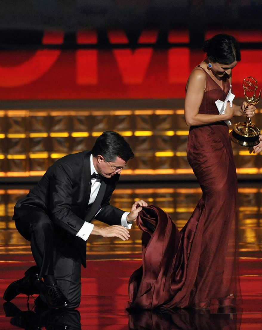 """Stephen Colbert holds onto the dress of Julia Louis-Dreyfus as she accepts the award for Outstanding Lead Actress in a Comedy Series for """"Veep"""" at the 64th Primetime Emmy Awards at the Nokia Theatre on Sunday, Sept. 23, 2012, in Los Angeles. (John Shearer/Invision/AP)"""