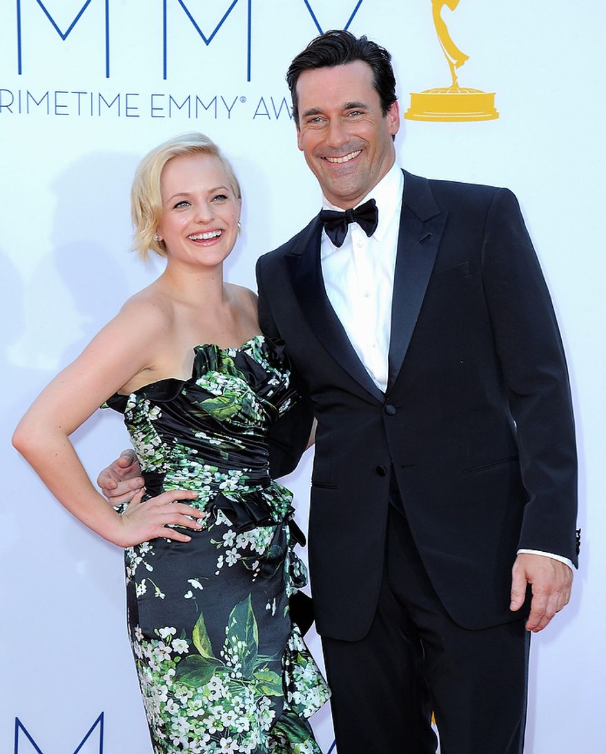Actress Elisabeth Moss, left, and actor Jon Hamm arrive at the 64th Primetime Emmy Awards at the Nokia Theatre on Sunday, Sept. 23, 2012, in Los Angeles.  (Photo by Jordan Strauss/Invision/AP)