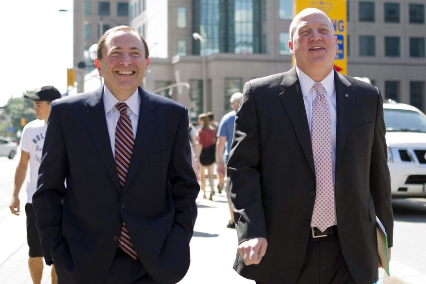 NHL commissioner Gary Bettman, left, and deputy commisioner and chief legal officer Bill Daly, Deputy Commissioner leave the NHLPA offices in Toronto on Wednesday, Aug. 22, 2012. Negotiations continue between the NHL and the NHLPA over collective bargaining as both sides try to avoid a potential lockout. (AP Photo/The Canadian Press, Chris Young)