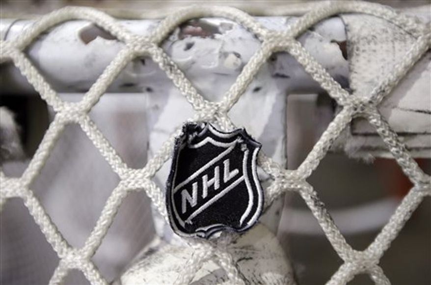 The NHL logo is seen on a goal at a Nashville Predators practice rink on Monday, Sept. 17, 2012, in Nashville, Tenn. The NHL has locked out its players, the fourth shutdown for the NHL since 1992. (AP Photo/Mark Humphrey)