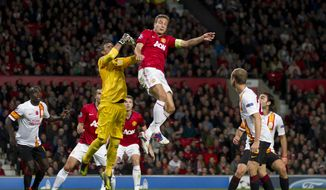 Manchester United's Nemanja Vidic, jumps for the ball against Galatasaray's goalkeeper Fernando Musera during their Champions Graoup H soccer match at Old Trafford Stadium, Manchester, England, Wednesday, Sept. 19, 2012. (AP Photo/Jon Super)