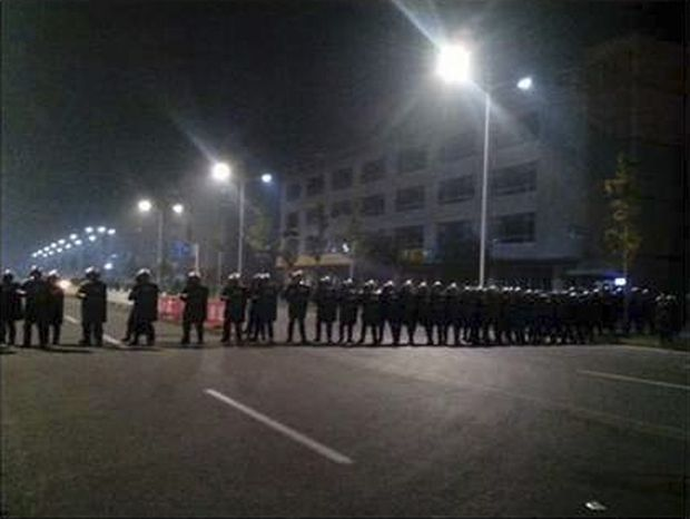 Police in anti-riot suits cordon off a road near Foxconn's plant in Taiyuan, China, in this Monday, Sept. 24, 2012, mobile phone photo. A brawl by as many as 2,000 Foxconn employees at a nearby dormitory injured 40 people. (AP Photo)