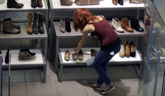 **FILE** A clerk straightens out her display at a shoe store in Salem, N.H., on Sept. 10, 2012. (Associated Press)