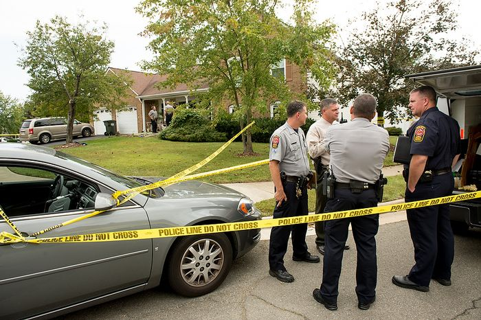 Fairfax police officers investigate the death of four family members discovered around 12pm after individuals had failed to show up to work, Herndon, Va., Tuesday, September 25, 2012. (Andrew Harnik/The Washington Times)