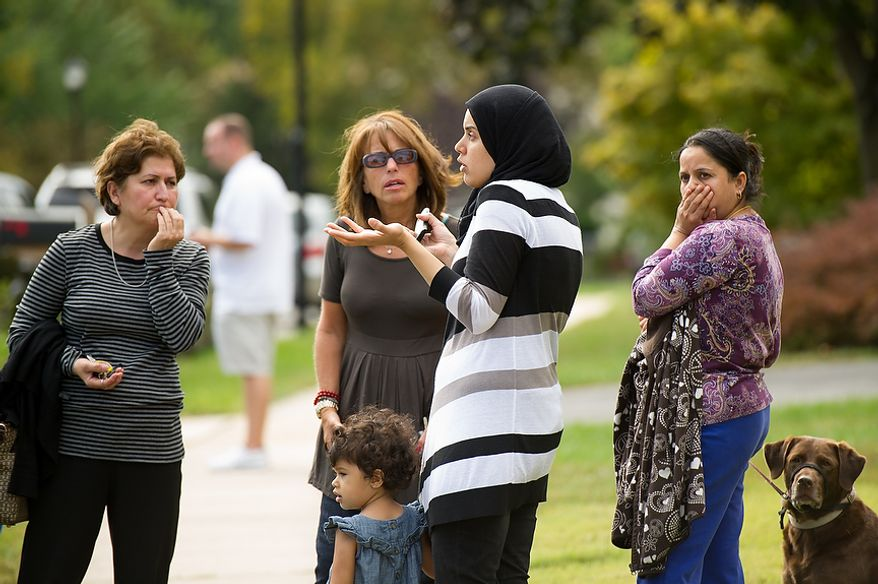 Neighbors talk outside a home that Fairfax police officers are investigating the death of four family members discovered around 12pm after individuals had failed to show up to work, Herndon, Va., Tuesday, September 25, 2012. (Andrew Harnik/The Washington Times)