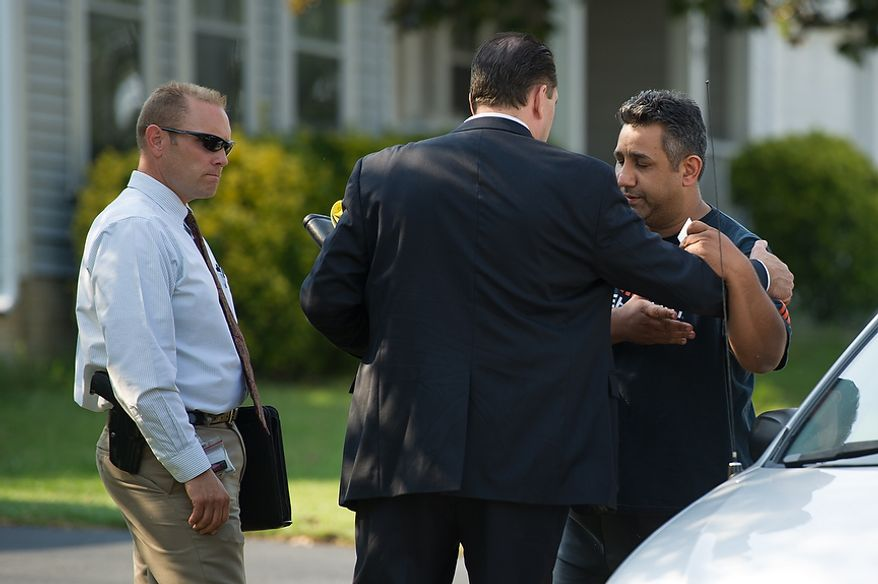 A man appears visibly distraught, right, as he speaks to Fairfax police detectives Rich Mullins, left, and Brian Colligan, second from left, who are investigating the death of four family members discovered around 12pm after individuals had failed to show up to work, Herndon, Va., Tuesday, September 25, 2012. The detectives would not release the mans name or if he was related to the family but they would confirm that he is a person involved in the ongoing investigation. (Andrew Harnik/The Washington Times)
