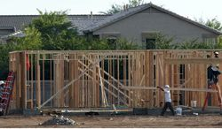**FILE** Workers frame a home on July 11, 2012, in Gilbert, Ariz., 20 miles outside Phoenix. (Associated Press)