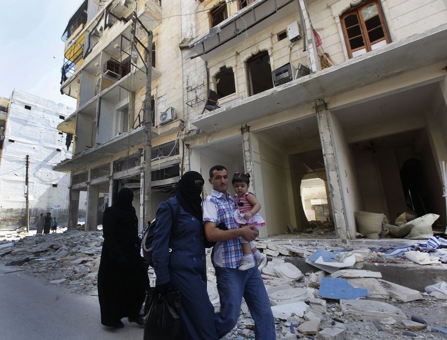 A Syrian family walks down a street that was destroyed in an Assad-regime airstrike earlier in the day in the al-Shaar neighborhood of Aleppo, Syria, on Monday, Sept. 24, 2012. (AP Photo/Hussein Malla)