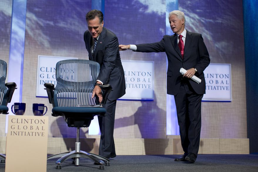 Former President Bill Clinton reaches out for Republican presidential candidate Mitt Romney as he grabs his notes after speaking at the Clinton Global Initiative convention in New York on Sept. 25, 2012. (Associated Press)