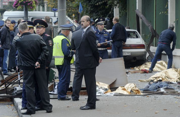 Law enforcement authorities work at the site of a Sept. 22, 2012, crash where a heavily drunk driver killed seven people at a bus stop in Moscow. Five orphaned teens were waiting for a bus with their guardians when a car careened into them, killing all seven. (Associated Press)