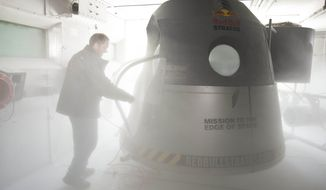 A crew member adjusts the space capsule of the Red Bull Stratos mission in the pressure chamber at Brooks Air Force Base in San Antonio on Sept. 24, 2012. Skydiver Felix Baumgartner Baumgartner will attempt to go supersonic when he jumps from the capsule at a record altitude of 23 miles over New Mexico. (Associated Press/Red Bull, Garth Milan)