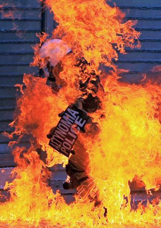 A riot police officer catches on fire after a petrol bomb thrown by protesters ignited during a nationwide general strike in Athens on Wednesday. Police clashed with protesters hurling petrol bombs and bottles in Athens on Wednesday after an anti-government rally called as part of a general strike turned violent. (Associated Press)
