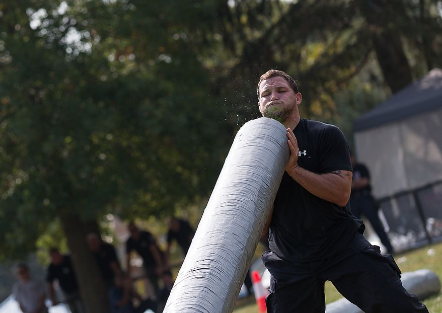 Officer Esron Montesino, assigned to Metro Transit in Washington D.C., flips a log weighing hundreds of pounds at the Iron Team Endurance Competition in Laurel, MD., Wednesday, September 26, 2012. The competition is hosted by the Prince George's County Police where teams from all over the east coast, including the Marines, compete in a grueling physical endurance challenge.(Andrew S. Geraci/The Washington Times)