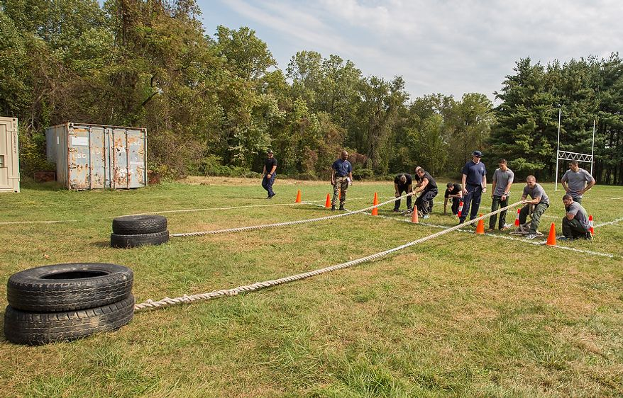 Officers assigned to Metro Transit in Washington D.C., pull tires across a field at the Iron Team Endurance Competition in Laurel, MD., Wednesday, September 26, 2012. The competition is hosted by the Prince George's County Police where teams from all over the east coast, including the Marines, compete in a grueling physical endurance challenge.(Andrew S. Geraci/The Washington Times)