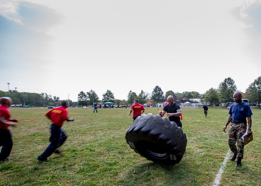 Officer Matt Harbison, assigned to Metro Transit in Washington D.C., flips a tire weighing hundreds of pounds at the Iron Team Endurance Competition in Laurel, MD., Wednesday, September 26, 2012. The competition is hosted by the Prince George's County Police where teams from all over the east coast, including the Marines, compete in a grueling physical endurance challenge.(Andrew S. Geraci/The Washington Times)