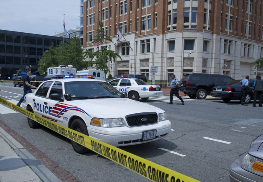 **FILE** FBI and Metropolitan Police Department officials surround the Family Research Council building in northwest Washington on Aug. 15, 2012, following the shooting of a security guard at the conservative Christian lobbying group. The guard was shot in the arm before wrestling the gunman to the ground. (Barbara L. Salisbury/The Washington Times)