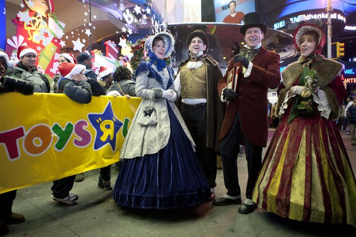 **FILE** Carolers perform for customers waiting in line outside the Toys R Us in Times Square in New York on Nov. 24, 2011. (Associated Press)