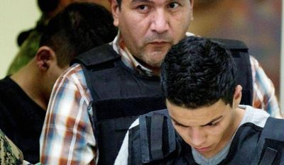 Ivan Velazquez Caballero is escorted to a news conference in Mexico City on Thursday after his arrest. Authorities say he leads a drug cartel faction. (Associated Press)