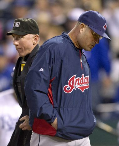 FILE - This Sept. 22, 2012 file photo shows Cleveland Indians manager Manny Acta, right, walking past home plate umpire Lance Barksdale during the fifth inning of a baseball game at Kauffman Stadium in Kansas City, Mo. The Indians have fired Acta after the team collapsed from contention. The Indians announced Acta will not return in 2013 on Thursday, Sept. 27, 2012, an off day before opening their final homestand. (AP Photo/Orlin Wagner, File)