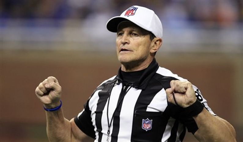 FILE - In this Dec. 24, 2011, photo, referee Ed Hochuli signals during the second quarter of an NFL game between the Detroit Lions and the San Diego Chargers in Detroit. The NFL and referees' union reached a tentative agreement on Wednesday, Sept. 26, 2012, to end a three-month lockout that triggered a wave of frustration and anger over replacement officials and threatened to disrupt the rest of the season. (AP Photo/Carlos Osorio, File)