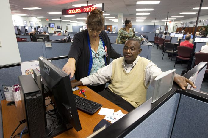 WorkForce One staffer Rose Capote-Marcus helps client Pen Osuji as he works on job applications at the Hollywood, Fla., unemployment office on Friday, Sept. 7, 2012. (AP Photo/J. Pat Carter)