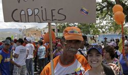 """A man and his daughter pose Sept. 1, 2012, with a poster that reads in Spanish, """"I'm a socialist and will vote for Capriles,"""" at a campaign rally in Miranda, Venezuela. A segment of President Hugo Chavez supporters have been turning away from the president and considering opposition presidential candidate Henrique Capriles. (Associated Press)"""