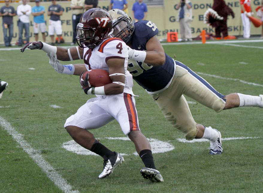 Virginia Tech running back J.C. Coleman (4) is hauled down by Pittsburgh defensive lineman Devin Cook (92) in the backfeld in the NCAA football game, Saturday, Sept. 15, 2012 in Pittsburgh. Pittsburgh upset Virginia Tech 35-17. (AP Photo/Keith Srakocic)