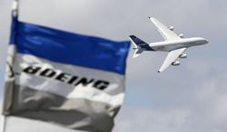 A Boeing flag flutters as an Airbus A380 makes a demonstration flight at the 49th Paris Air Show at Le Bourget Airport near Paris in 2011. (AP Photo/Francois Mori)