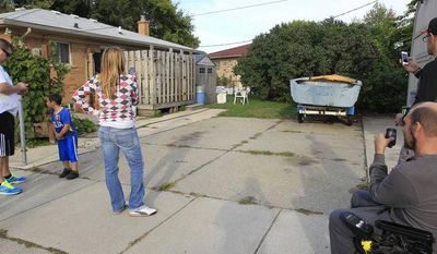 People take photographs Sept. 26, 2012, of a driveway in Roseville, Mich., that a tipster said could be the final resting place of missing Teamsters leader Jimmy Hoffa. Authorities plan to take soil samples from under the driveway. (Associated Press)