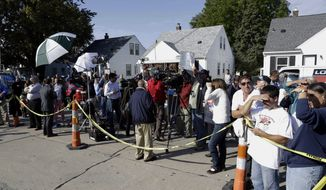 ** FILE ** The media and spectators watch as authorities drill for soil samples in the floor at a Roseville, Mich., home on Sept. 28, 2012. Police have been told by a source that former Teamsters boss Jimmy Hoffa may be buried beneath a driveway. (Associated Press)