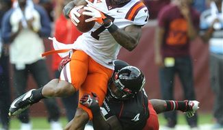 Virginia Tech's Marcus Davis (7) tries to get away from Cincinnati's Maalik Bomar (4) after he caught a pass for a first down during the first half of an NCAA college football game, Saturday, Sept. 29, 2012, in Landover, Md. (AP Photo/Richard A. Lipski)