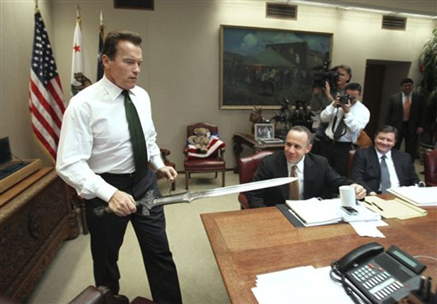 """** FILE ** In this Jan. 13, 2009, file photo, Gov. Arnold Schwarzenegger brings the sword he used in the movie """"Conan The Barbarian,"""" to the conference table before the start of budget negotiations with legislative leaders at the Capitol in Sacramento, Calif. Schwarzenegger, who came to office during California's historic 2003 recall election, is releasing his autobiography, """"Total Recall: My Unbelievably True Life Story."""" (AP Photo/Rich Pedroncelli, file)"""