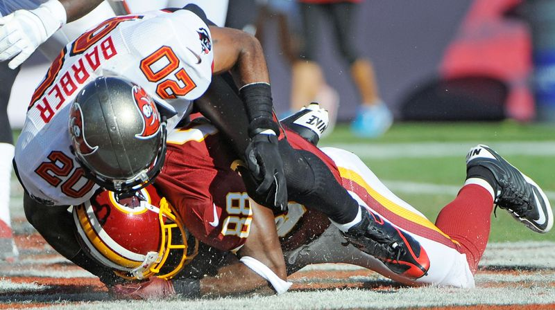 associated press Redskins receiver Pierre Garcon is hit by Buccaneers safety Ronde Barber as he recovers a fumble by quarterback Robert Griffin III in the end zone for a touchdown during the first quarter.