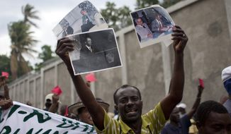 A demonstrator holds signs with images of former Haitian President Jean Bertrand Aristide during a protest against President Michel Martelly's government in Port-au-Prince, Haiti, on Sunday, Sept. 30, 2012. (AP Photo/Dieu Nalio Chery)