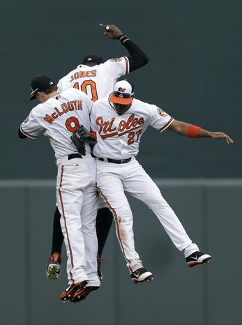 Baltimore Orioles' Nate McLouth, left, Adam Jones (10) and Endy Chavez celebrate after a baseball game against the Boston Red Sox in Baltimore, Sunday, Sept. 30, 2012. Baltimore won 6-3. (AP Photo/Patrick Semansky)