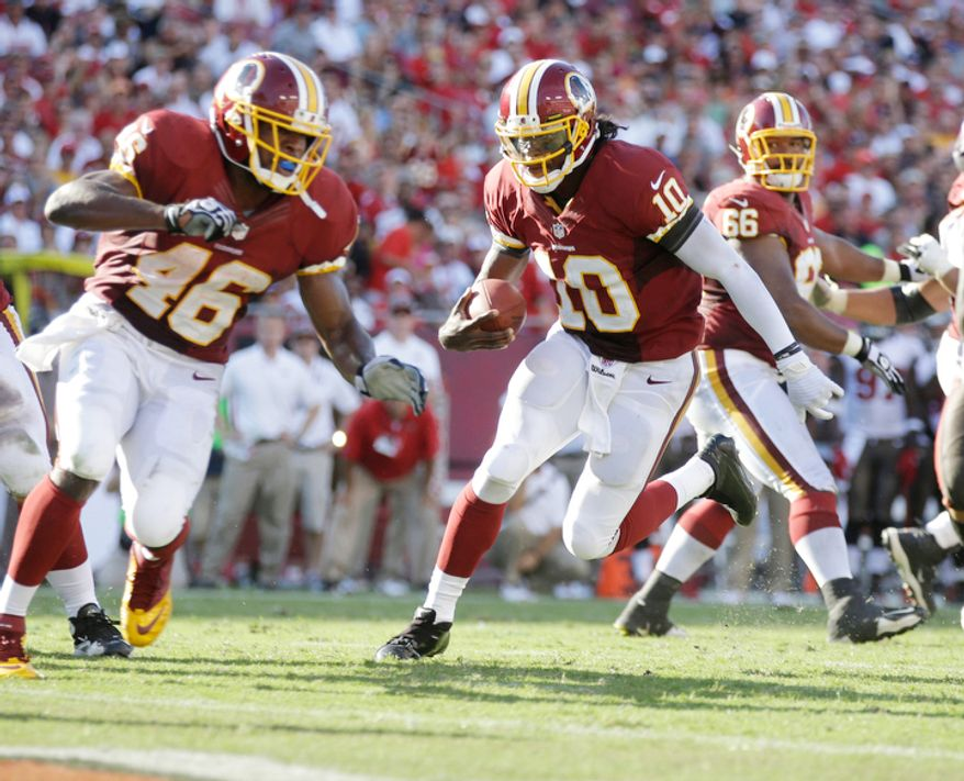 Washington Redskins quarterback Robert Griffin III (10) scores a touchdown during an NFL game between the Redskins and the Tampa Bay Buccaneers.   (AP Photo/Margaret Bowles)