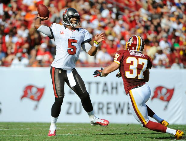 Tampa Bay Buccaneers quarterback Josh Freeman (5) throws a pass as he is pressured by Washington Redskins strong safety Reed Doughty (37) during the first quarter. (AP Photo/Brian Blanco)