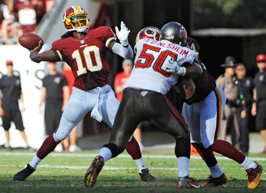 Washington Redskins quarterback Robert Griffin III (10) throws a pass as he is pressured by Tampa Bay Buccaneers defensive tackle Daniel Te'o-Nesheim (50) during the second quartera. (AP Photo/Brian Blanco)