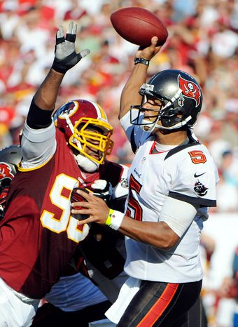 Tampa Bay Buccaneers quarterback Josh Freeman (5) throws an interception as he is pressured by Washington Redskins nose tackle Barry Cofield (96) during the second quarter. (AP Photo/Brian Blanco)