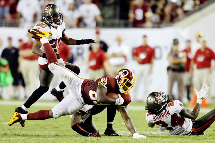 Washington Redskins tight end Logan Paulsen (82) gets taken down by Tampa Bay Buccaneers strong safety Mark Barron (24) and free safety Ronde Barber (20) during the fourth quarter. (AP Photo/Chris O'Meara)