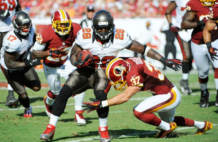 Tampa Bay Buccaneers running back D.J. Ware (28) is hit by Washington Redskins strong safety Reed Doughty (37) during an NFL football game Sunday, Sept. 30, 2012, in Tampa, Fla. (AP Photo/Brian Blanco)