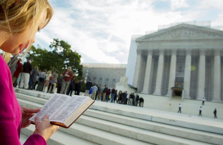 A woman holds a Bible while standing in silent prayer on the steps of the Supreme Court on Oct. 1, 2012, before the justices return to the benc