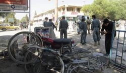 Police secure the site of a suicide bombing in Khost, Afghanistan, on Monday, Oct. 1, 2012, after a bomber drove a motorcycle packed with explosives into a patrol of Afghan and international forces, killing more than a dozen people, including three NATO service members and their translator, officials said. (AP Photo/Nashanuddin Khan)