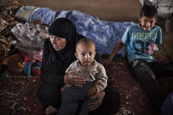 A displaced Syrian woman and her grandson sit Sept. 30, 2012 in a refugee camp on the Turkey border, near Azaz village in Syria. (Associated Press)