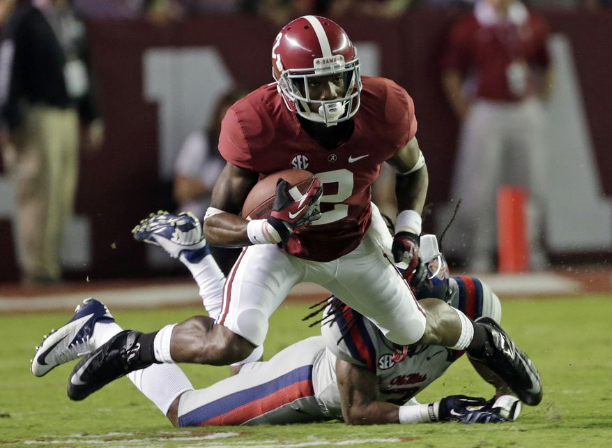 Alabama wide receiver DeAndrew White (2) is tripped up by Ole Miss defensive back Charles Sawyer (3) in the first half of an NCAA college football game at Bryant-Denny Stadium in Tuscaloosa, Ala., Saturday, Sept. 29, 2012. White was injured on the play. (AP Photo/Dave Martin)