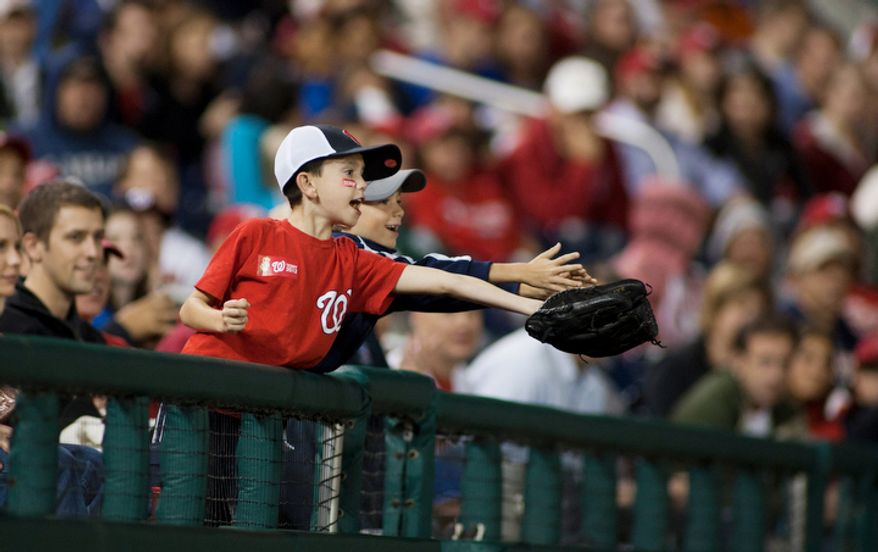 Washington National kids reach for a foul ball in the second inning. (Craig Bisacre/The Washington Times)