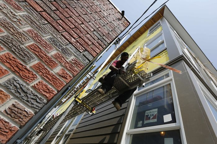 A construction worker adjusts a scaffold at the site of a new residential project in the East Boston neighborhood of Boston on Friday, Aug. 17, 2012. (AP Photo/Michael Dwyer)