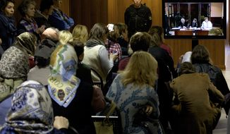 Lawyers for the feminist punk band Pussy Riot are pictured on a TV screen outside a courtroom in Moscow on Monday Oct. 1, 2012. (AP Photo/Ivan Sekretarev)