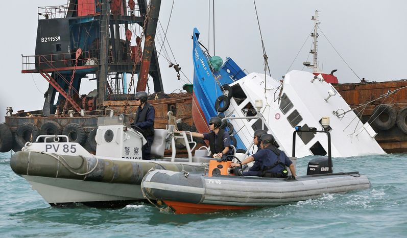 Associated Press Police officers guard the partially submerged Lamma IV after it collided with a ferry off the southwestern coast of Hong Kong on Tuesday, kil